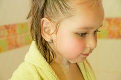 Liten härlig flicka som spelar ta en dusch i bad med en gul badrock Arkivbild
