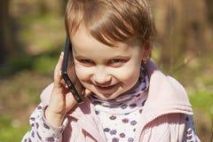 Liten härlig flicka som talar på smartphonekommunikationen, royaltyfria bilder