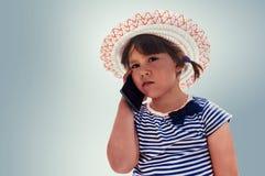 Liten härlig flicka som talar på smartphonen arkivbild