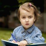Liten härlig flickahandstil i hennes bokutbildning, kunskap, arkivfoton