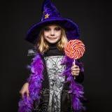 Liten härlig halloween häxa med den färgrika godisen Fotografering för Bildbyråer