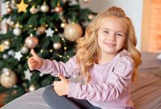 Liten härlig lockig blond flicka som sitter på sängen och ler på bakgrunden av julgranen arkivfoto