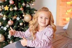 Liten härlig lockig blond flicka som sitter på sängen och ler på bakgrunden av julgranen royaltyfri fotografi