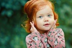 Liten härlig rödhårig liten flicka som lyckligt ler, i summ Arkivfoton