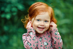 Liten härlig rödhårig liten flicka som lyckligt ler, i summ Arkivbild