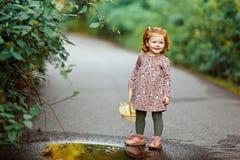 Liten härlig rödhårig liten flicka som lyckligt ler, i summ royaltyfria bilder
