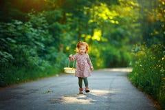 Liten härlig rödhårig liten flickaspring på banan, in arkivfoto