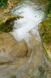 Liten härlig vattenfall som omges av skogar och berg Arkivbilder