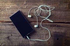 Liten hörlurar med mobiltelefonen Royaltyfri Bild