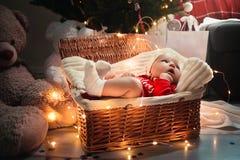 Liten halkning behandla som ett barn pojken med julkläder i korgjulgarnering och pråliga ljus runt om henne arkivfoton