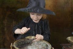 Liten halloween häxa med kitteln arkivfoton