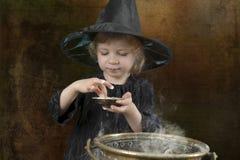 Liten halloween häxa med kitteln fotografering för bildbyråer