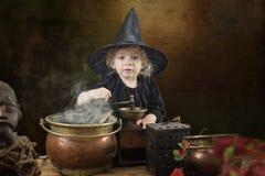 Liten halloween häxa med kitteln arkivbild