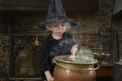 Liten halloween häxa med kitteln royaltyfria bilder