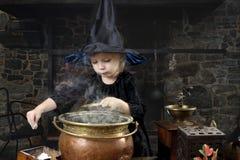 Liten halloween häxa med kitteln arkivfoto