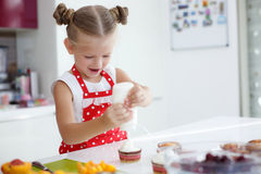 Liten hemmafru som är förlovad i stekheta muffin i köket hemma Royaltyfri Fotografi