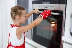 Liten hemmafru som är förlovad i stekheta muffin i köket hemma Arkivfoton