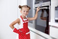 Liten hemmafru som är förlovad i stekheta muffin i köket hemma Arkivfoto
