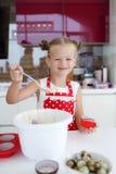 Liten hemmafru som är förlovad i stekheta muffin i köket hemma Arkivbild