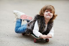 Liten hipsterflicka med skateboardståenden Royaltyfria Foton