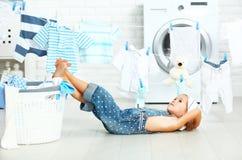 Liten hjälpreda tröttad barnflicka som tvättar kläder och som vilar i laund Arkivbild