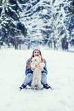 Liten hund med ägaren att spendera en dag på vinterskogen royaltyfri foto