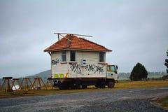 Liten husvagn som används som permanent hem med konkreta taktegelplattor, på en lastbil Royaltyfri Foto