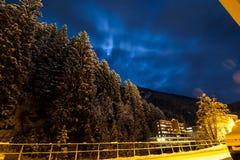Liten by i natten under vinter i fjällängarna Arkivbild