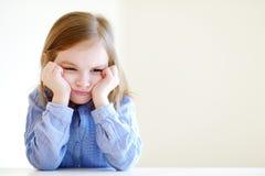 Liten ilsken eller uttråkad flickastående Arkivbild