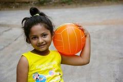 Liten indisk flicka som rymmer en boll på hennes skuldra med lyckligt uttryck, Pune arkivbild