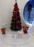 Liten julgran med röda och guld- prydnader arkivbild