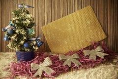 Liten julgran på en träbakgrund för vykort och Arkivbild