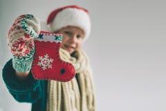 Liten julsocka i händer på flickan Barnet är den iklädda tröjan, jul hatt och halsdukstudioskottet royaltyfri foto