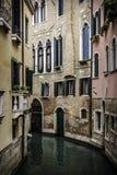 Liten kanal bland hus i Venedig arkivbild