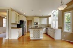 Liten klassisk amerikansk kökinre med det vita kabinetter och ädelträgolvet Arkivbild