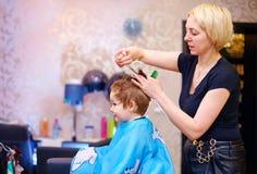 Liten klient, pojke som har frisyr på hårsalongen Arkivfoton