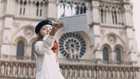 Liten konstnär i svart basker och röd halsdukteckning i anteckningsbok nära Notre Dame i Paris, Frankrike, berömd domkyrka arkivfilmer