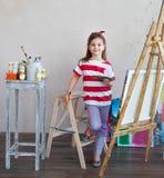 Liten konstnärflicka som rymmer en målarpensel och ser över en canva Royaltyfria Foton