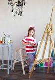 Liten konstnärflicka som rymmer en målarpensel och ser över en canva Royaltyfri Bild