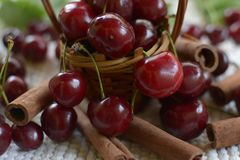 Liten korg med handtaget, kanelbruna stänger för röda körsbär på vit Fotografering för Bildbyråer