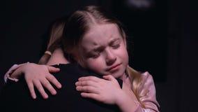 Liten kvinnlig unge som kramar modern och gråter, offer av familjevåld, skräck arkivfilmer