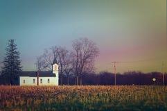 Liten kyrka i bygden av Iowa för den horisontalsolnedgången Royaltyfri Foto