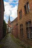 Liten kyrka och gata på Bruges Arkivbilder