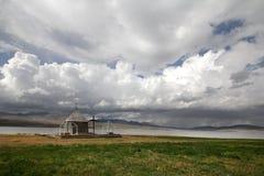 Liten kyrka under ett enormt vitt moln i byn av Foka royaltyfri fotografi