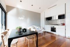 Liten lägenhet för öppet plan med pentryt som äter middag tabellen och soffan Arkivbild