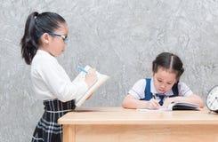 Liten lärarehandstil på boken och student borrade till att göra homewo Royaltyfri Bild