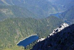 Liten lake Riza som omges av berg som är forested Arkivbilder