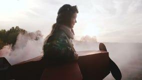 Liten le pilot- flicka som rotera i roligt pappflygplan med färgrök på härlig solnedgångfältultrarapid stock video