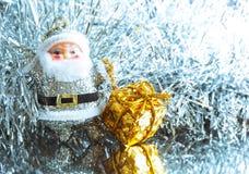 Liten leksak Santa Claus med gåvor på en briljant ljus silverbakgrund Royaltyfri Bild