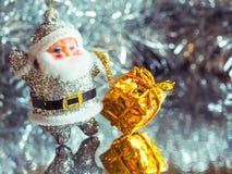 Liten leksak Santa Claus med gåvor på en briljant ljus silverbakgrund tonat Royaltyfri Bild